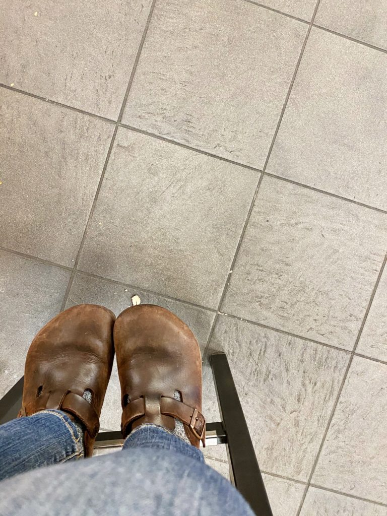 photo of feet in clogs hanging off support beam on chair