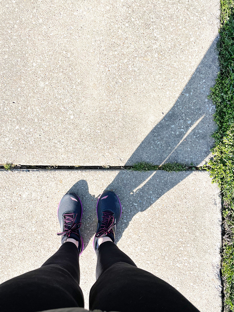 Author's feet in trainers on sidewalk with long shadow