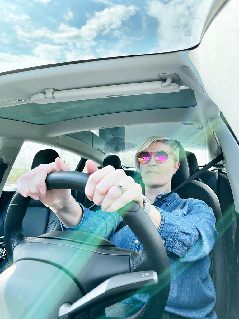 Author driving a car with hands on the steering wheel in the foreground