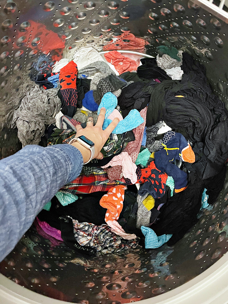 Author's left hand reaching into a washing machine to grab a handful of colorful clothing items