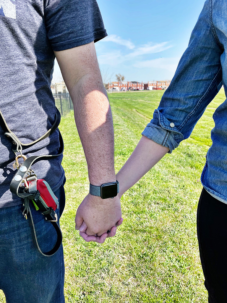 Author holding hands with husband with a background of green grass and blue sky