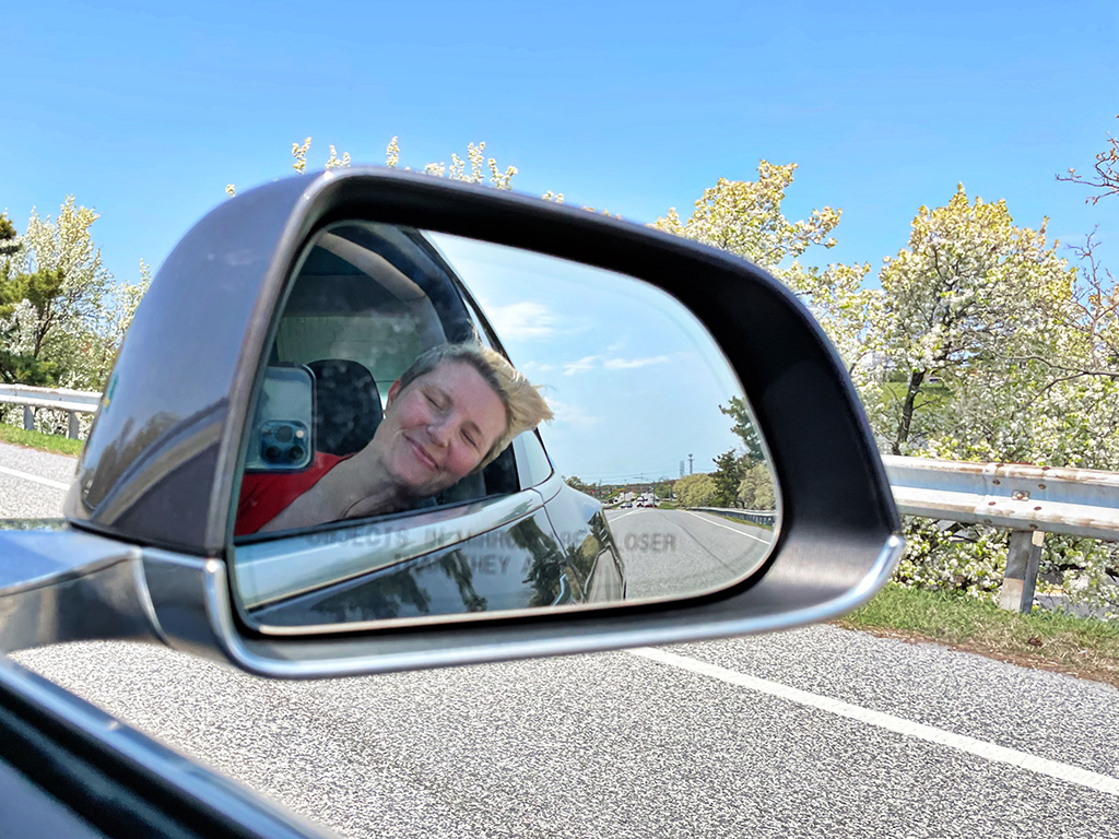 Author's reflection in car's side mirror of head out window