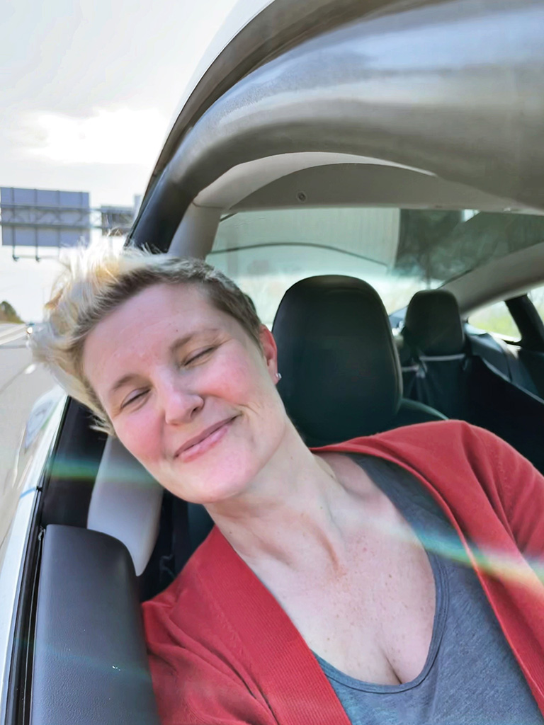 Author with head out car window smiling with eyes closed and hair blowing in wind
