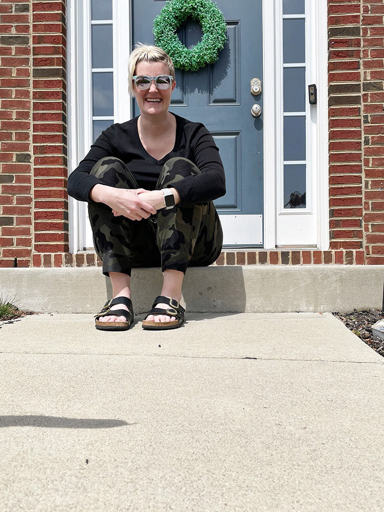 Author sitting on step in front of house wearing sunglasses
