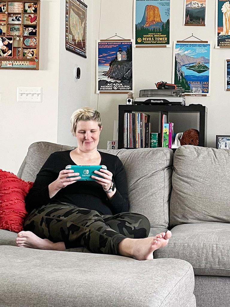 Author sitting on couch holding a Nintendo Switch